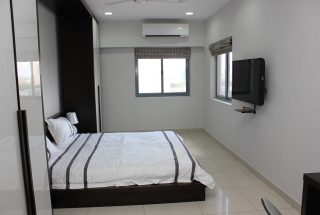 Bedroom with TV of the Two Bedroom Furnished Apartment in Upanga Dar es Salaam by Tanganyika Estate Agents