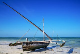 A dhow sitting on the beach in front of the Two Villa Hotel for Sale in Jambiani, Zanzibar by Tanganyika Estate Agents